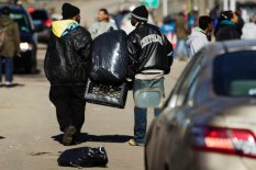Residents work together to carry container of donated clothing left on street for victims of superstorm Sandy in Rockaways neighborhood of the Queens borough