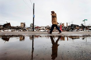 A man walks past buildings destroyed by a fire that took place during hurricane Sandy and through snow left on the ground after a nor'easter, also known as a northeaster storm in the Queens borough neighborhood of Rockaway Park