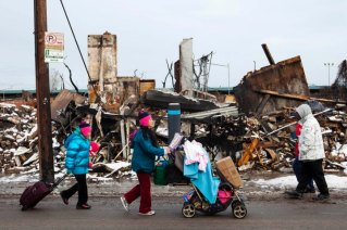 People push carts with donated items in them past buildings destroyed by a fire that took place during hurricane Sandy and through snow left on the ground after a nor'easter in the Queens borough neighborhood of Rockaway Park