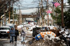 Residents walk down a street past piles of debris piled up outside of people's homes due to the flooding from hurricane Sandy that are covered in snow left by a nor'easter in the Queens borough neighborhood of Rockaway Beach