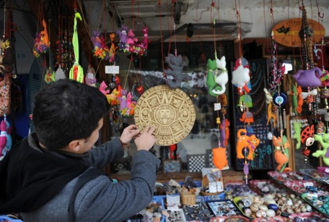 TURKEY: A tourist looks at doomsday products on sale in Sirince, a village in western Turkey. Some believed Sirince was the only safe haven from the apocalypse because it is where the Virgin Mary is said to have risen to heaven