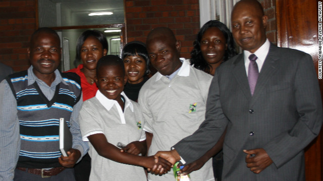 "Maud shakes hands with Gershem Pasi, commissioner general of ZIMRA. ""At 14, she has achieved a rare feat which some grown-ups have struggled to even initiate,"" said Pasi as he announced Maud's sponsorship package in late May, 2012"