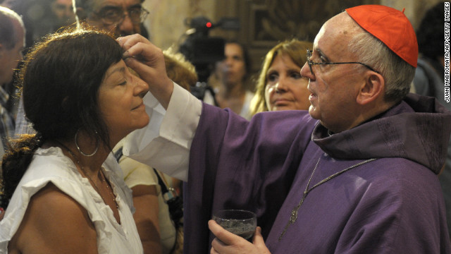 Bergoglio, right, draws the cross on the forehead of a parishioner during a Mass for Ash Wednesday, which begins the 40-day period of abstinence for Christians before the Holy Week and Easter, on February 13 at the Metropolitan Cathedral in Buenos Aires
