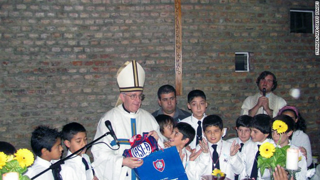 Bergoglio poses with school children and the emblem of Argentina's San Lorenzo football team